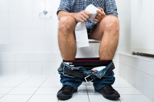 Man In Toilet Holding Tissue Paper Roll
